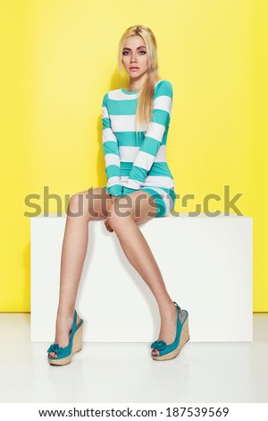 Beautiful young woman sitting in a trendy wedges shoes over yellow background - stock photo