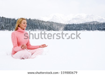 Beautiful young woman sitting in a yoga position on a frozen lake in the snow mountains landscape, meditating and contemplating the scenery during a winter day on holiday, outdoors. - stock photo