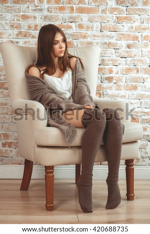 Beautiful Young Woman Sitting In Armchair On Brick Wall Background