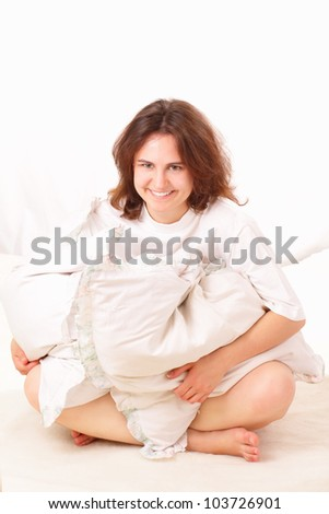 Beautiful young woman sitting in bed - stock photo