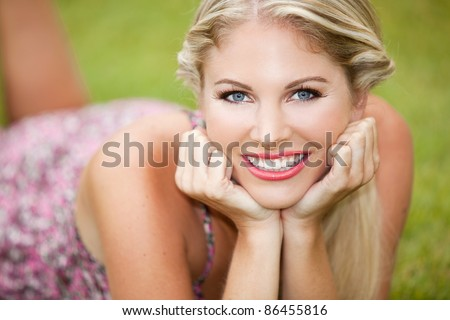 Beautiful young woman sitting in the grass - stock photo