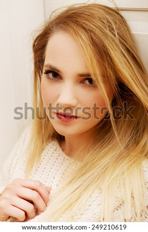 Beautiful young woman sitting in the kitchen at home. - stock photo