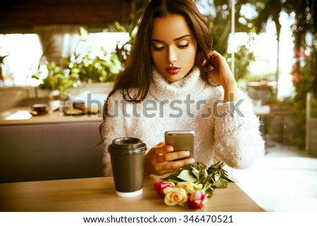 beautiful young woman sitting  in trendy urban coffee shop and texting message on her smartphone. Toned in warm colors. Indoors shot. Horizontal - stock photo
