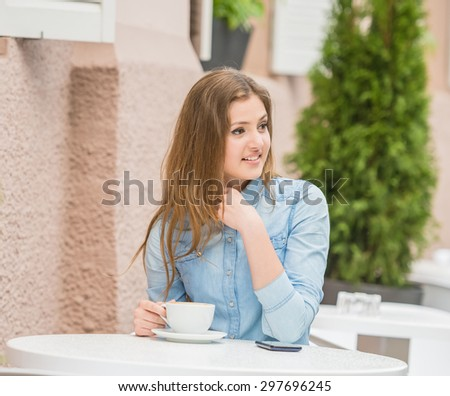 Beautiful young woman sitting in urban cafe and looking away on something amazing. - stock photo