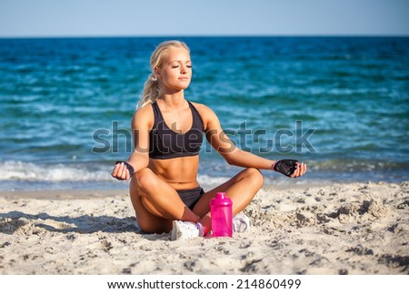 beautiful young woman sitting in yoga pose at the beach  - stock photo