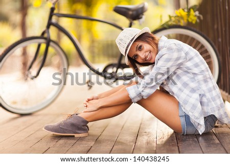 beautiful young woman sitting next to her bike outdoors - stock photo