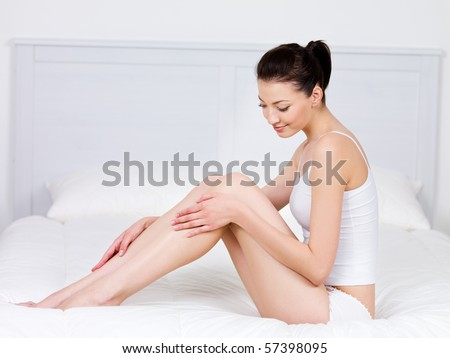 Beautiful young woman sitting on a bed and stroking her perfect legs - indoors - stock photo