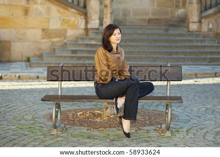 beautiful young woman sitting on a bench
