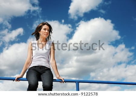 Beautiful young woman sitting on a border over cloudy blue sky. - stock photo