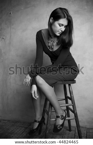 beautiful young woman sitting on a chair - stock photo