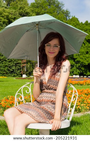 Beautiful young woman sitting on a chair in a park and holding her umbrella - stock photo