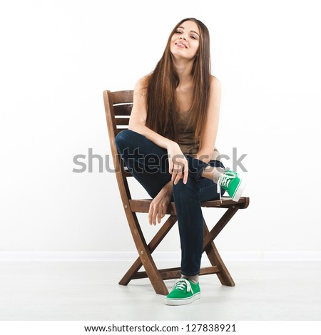 Beautiful young woman sitting on a chair over white background - stock photo