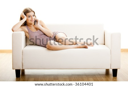 Beautiful young woman sitting on a couch and making a phone call