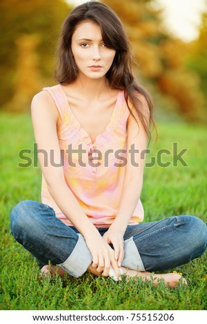 Beautiful young woman sitting on a green lawn in the lotus position - stock photo