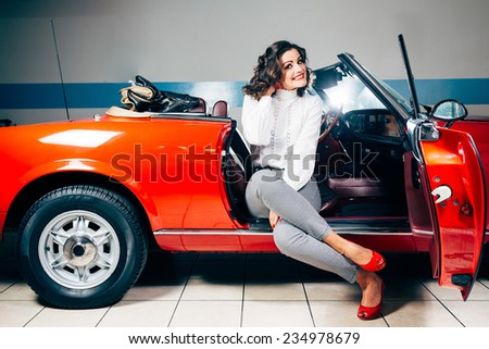 Beautiful young woman sitting on a red vintage car - stock photo