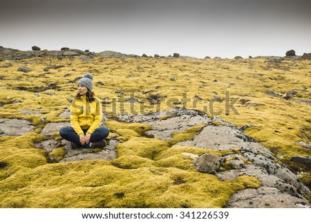 Beautiful young woman sitting on a rock and surrounded by Icelandic moss - stock photo