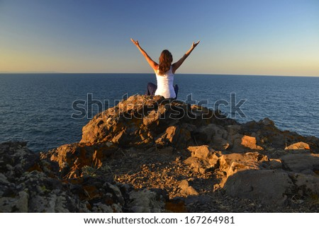 Beautiful young woman sitting on a rock contemplating the blue evening sea. - stock photo