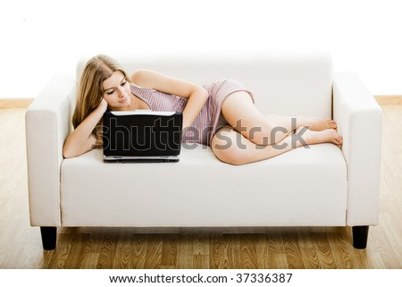 Beautiful young woman sitting on a sofa and working on a laptop