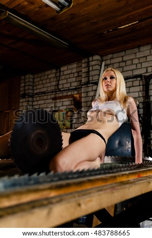 Beautiful young woman sitting on a table with big saw in the garage