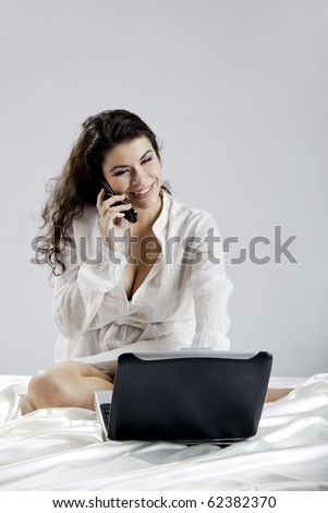 Beautiful young woman sitting on bed working with a laptop and making a phone call - stock photo