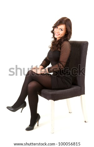 beautiful young woman sitting on chair, full length, white background