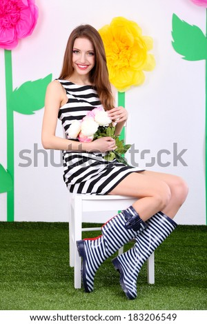 Beautiful young woman sitting on chair on decorative background - stock photo