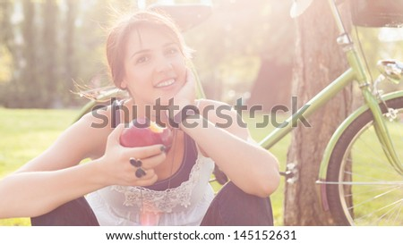 Beautiful young woman sitting on grass and eating apple next to her bike. - stock photo