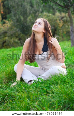 beautiful young woman sitting on green grass