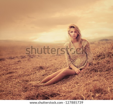 beautiful young woman sitting on hay. The picture shows a sunset - stock photo