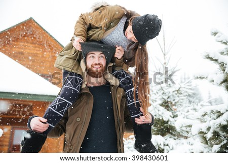 Beautiful young woman sitting on man shoulders and having fun in winter - stock photo