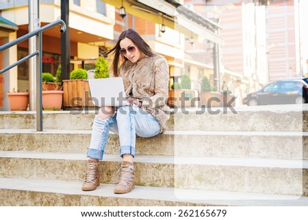 Beautiful young woman sitting on stairs, holding lap top and typing. Empty text box on the right side. Shallow depth of field. - stock photo