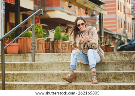 Beautiful young woman sitting on stairs, typing on the smart phone. Shallow depth of field. - stock photo