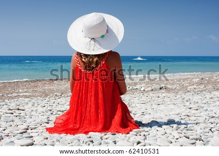 beautiful young woman sitting on the beach and looks at sea
