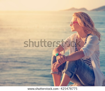 beautiful young woman sitting on the beach and watching the sunset - stock photo