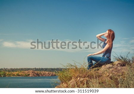 Beautiful young woman sitting on the cliff above the river, meditating with her eyes closed