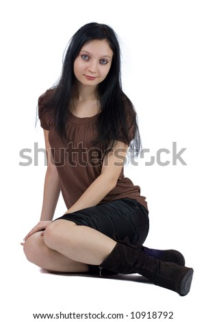 Beautiful young woman sitting on the floor isolated on white - stock photo
