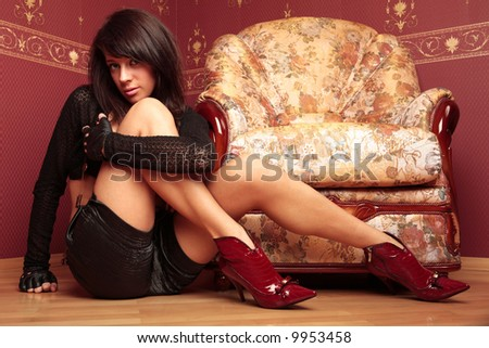 Beautiful young woman sitting on the floor near chair.