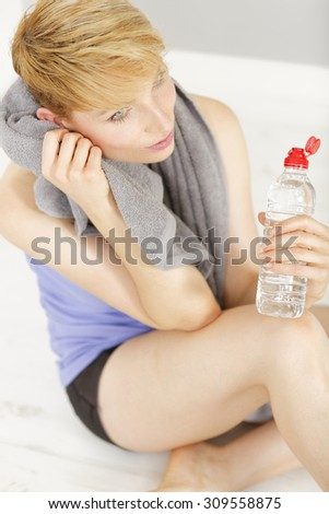 Beautiful young woman sitting on the floor relaxing after a long sports workout with a bottle of water