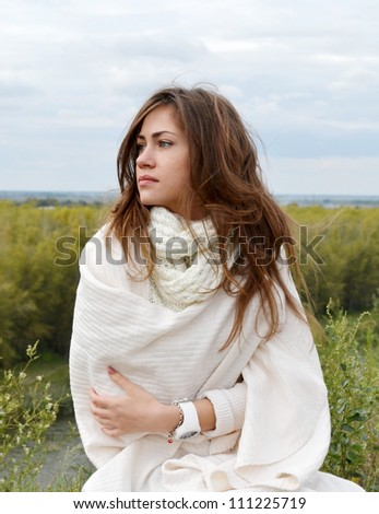 Beautiful young woman sitting on the grass - stock photo