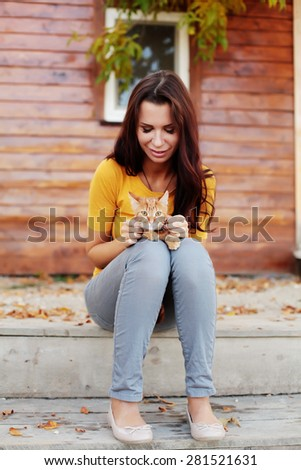 Beautiful young woman sitting on the porch and is holding her cat. - stock photo