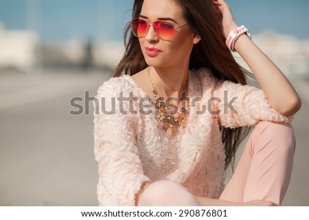 Beautiful young woman sitting on the road. beautiful young girl sitting on a way. Modern Youth Lifestyle Concept.. Woman outdoor portrait - stock photo