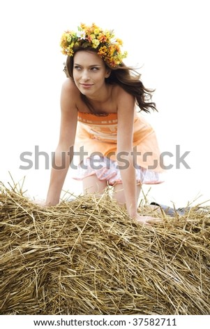 beautiful young woman sitting on the round bale of hay on a field