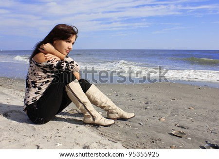 beautiful young woman sitting on the seashore