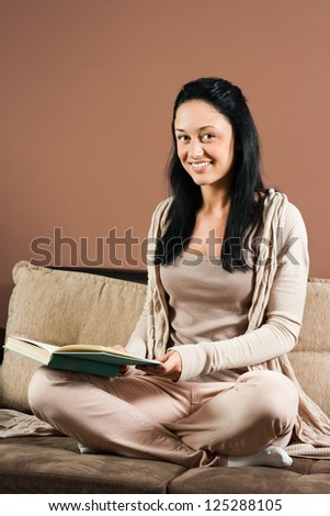 Beautiful young woman sitting on the sofa and reading a book,Young woman with a book - stock photo