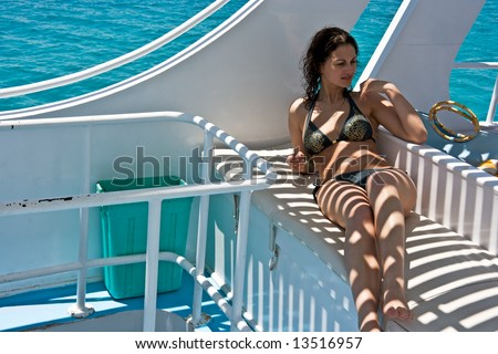 Beautiful young woman sitting on the yacht deck