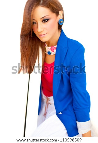 Beautiful young woman sitting over white background, attractive elegant female with long straight brown hair and stylish colors make-up, nice girl in colorful clothes and fashionable jewelery - stock photo