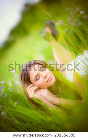 Beautiful young woman sleeping among the grass and flowers - stock photo