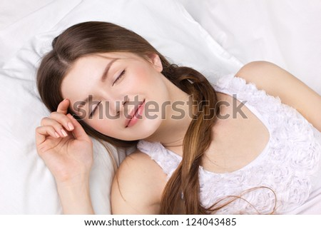 beautiful young woman sleeping in a white pajamas - stock photo