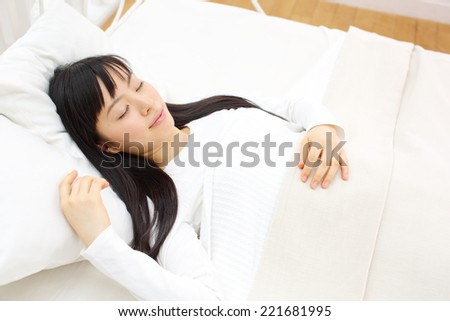 beautiful young woman sleeping in bed - stock photo