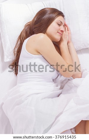 Beautiful young woman sleeping in the bed. Relaxing and peaceful